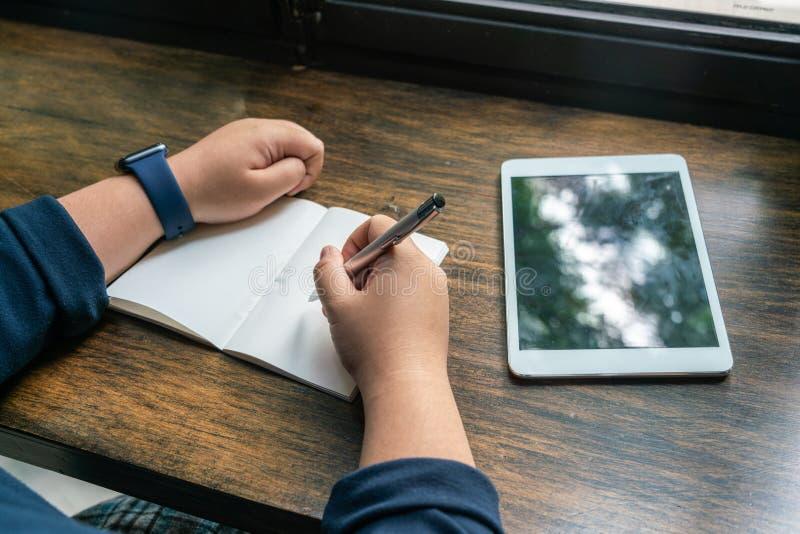 Pluma de tenencia humana asiática de la mano y escritura al lado de la tableta fotos de archivo