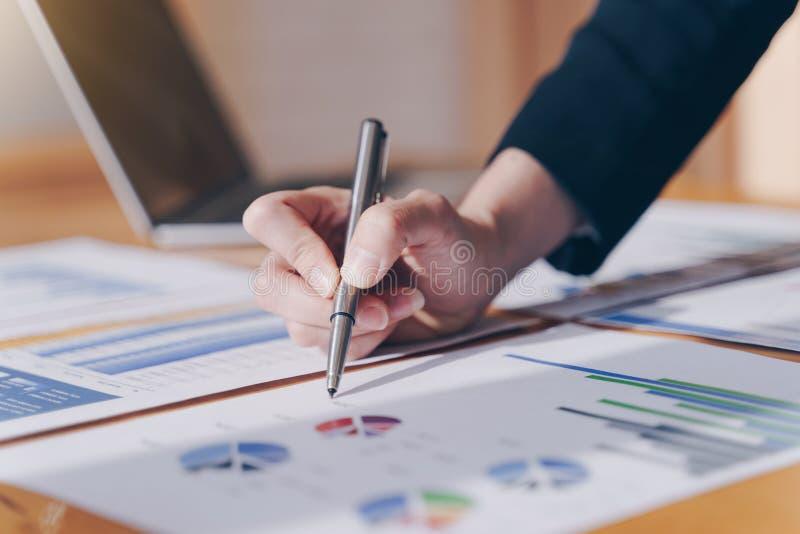 Pluma de tenencia de la empresaria que señala en carta del informe resumido y calcular finanzas en oficina imagenes de archivo