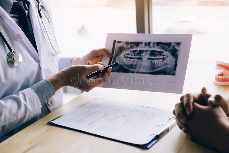 Pluma de tenencia de la mano del dentista que señala la imagen de la radiografía y que habla con el paciente sobre la medicación  foto de archivo libre de regalías