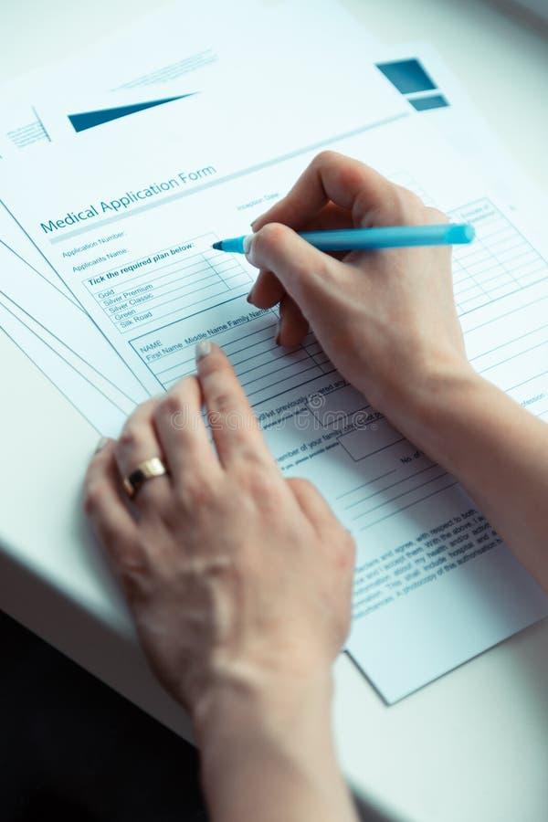 Pluma de tenencia de la mujer y papeles de firma que compran seguro médico imagen de archivo