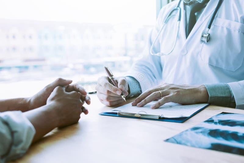 Pluma de tenencia masculina asiática de la mano del doctor que escribe la lista de la historia paciente imagen de archivo