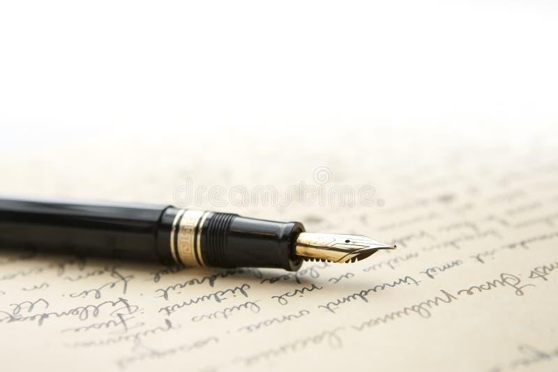 Pluma del oro con la carta y la escritura imagen de archivo