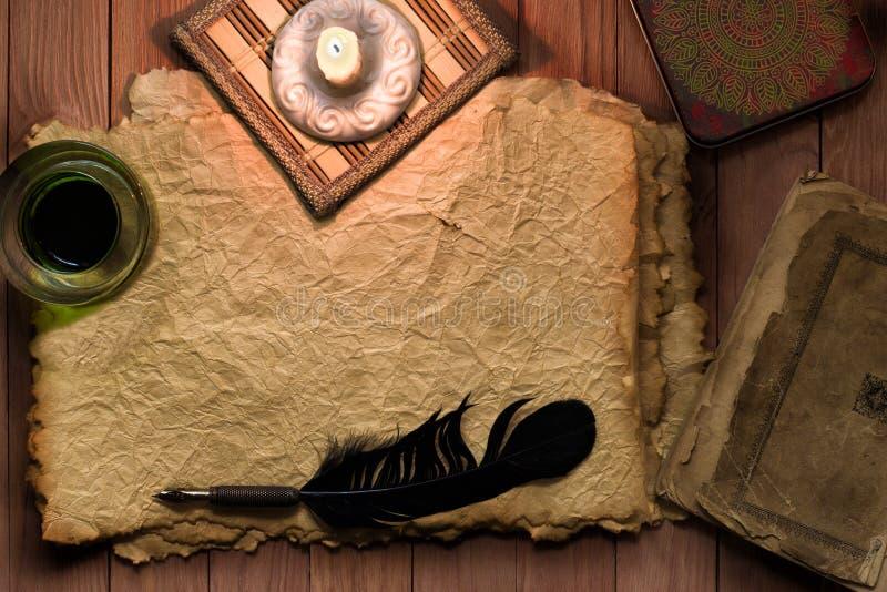 Pluma del vintage con el documento y la tinta sobre la tabla a la luz de la vela fotos de archivo libres de regalías