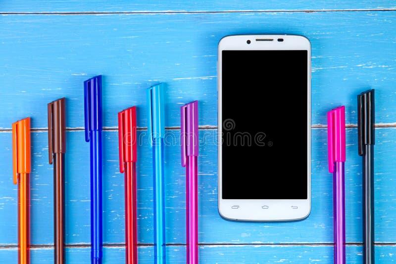 Pluma elegante del teléfono y del color en el fondo de madera azul imagen de archivo