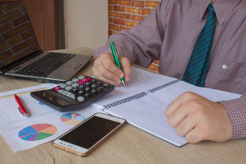 Pluma en cuentas del papeleo con el ordenador del uso del hombre para ahorrar datos en fondo Concepto de estadísticas Mano del ho imagen de archivo libre de regalías