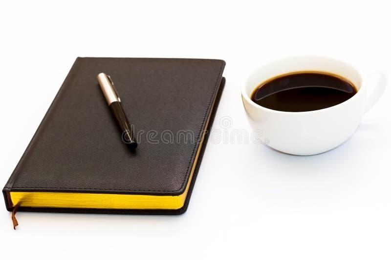 Pluma en el planificador negro del día y una taza de café sólo en un fondo blanco Concepto mínimo del negocio del lugar de trabaj fotos de archivo