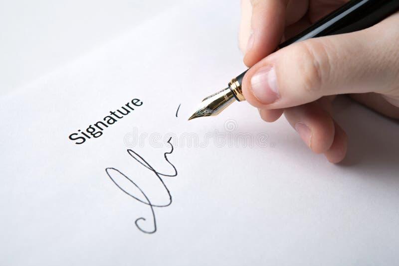 Pluma en la mano y la firma del hombre fotos de archivo libres de regalías