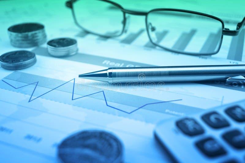 Pluma, gases, moneda y calculadora en la carta y el gráfico financieros, a fotos de archivo libres de regalías