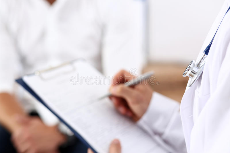 Pluma masculina de la plata del control de la mano del doctor que llena la lista de la historia paciente fotos de archivo