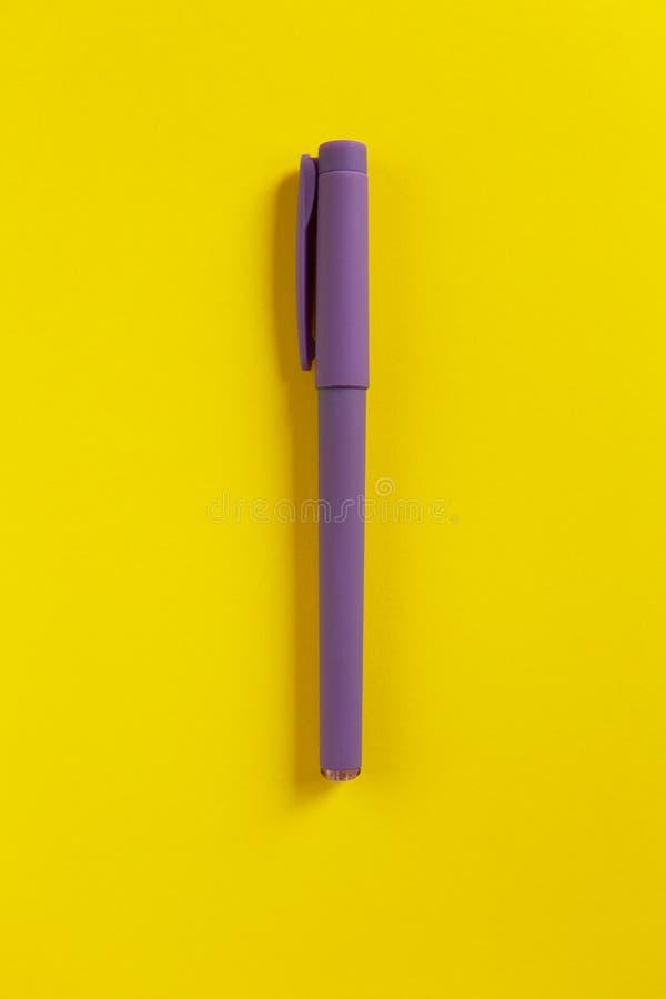 Pluma púrpura en fondo de papel amarillo Composici?n central De nuevo a escuela, concepto de la educaci?n Visi?n superior Endecha imagen de archivo libre de regalías