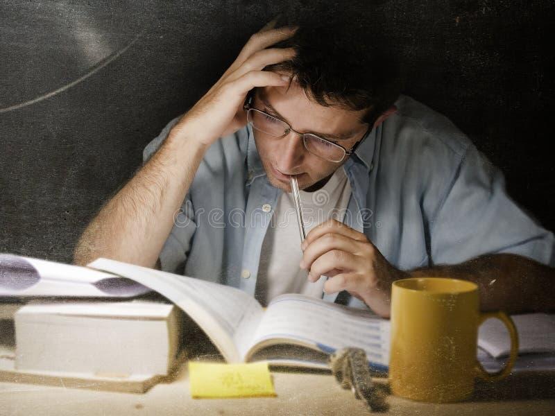 Pluma penetrante del estudiante en casa de la lectura joven del escritorio que estudia en la noche con la pila de libros y de caf fotos de archivo libres de regalías