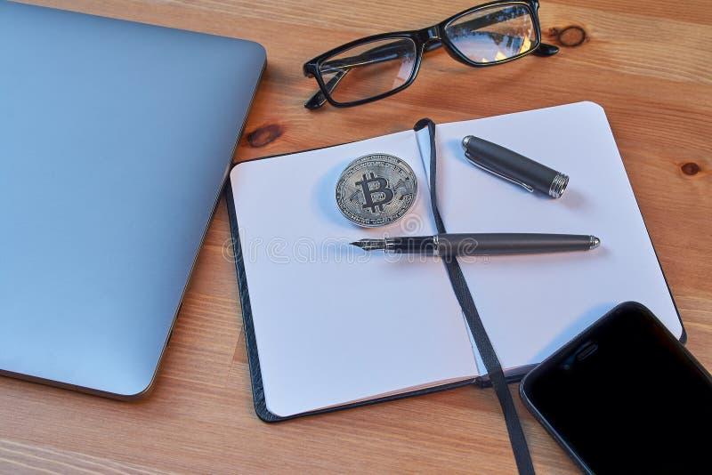 Pluma portátil de los vidrios, del cuaderno y de la escritura del teléfono móvil del ordenador portátil de Bitcoin de las monedas imagen de archivo