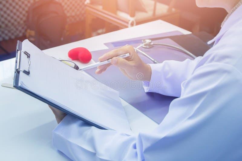 Pluma que se sostiene del doctor que señala plan del tratamiento contra el cáncer del informe en el escritorio imagen de archivo libre de regalías