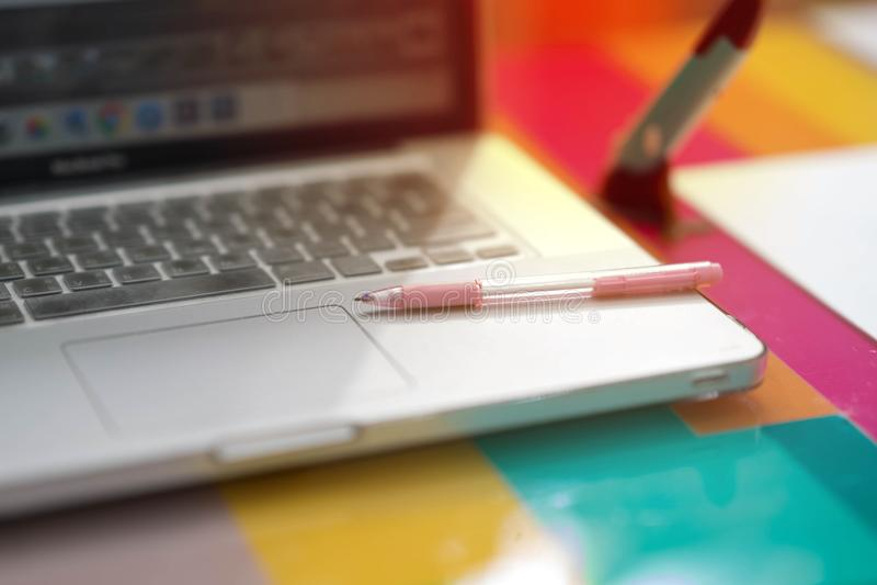 Pluma rosada en el cuaderno en el escritorio colorido en oficina y luz del sol imágenes de archivo libres de regalías
