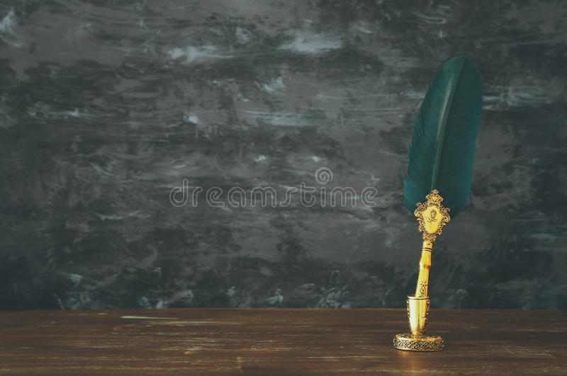 Pluma verde vieja de la tinta de la canilla de la pluma con el tintero sobre el escritorio de madera delante del fondo negro de l imágenes de archivo libres de regalías