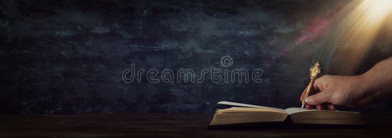 Pluma vieja de la tinta de la canilla de la pluma con el tintero y los libros viejos sobre el escritorio de madera delante del fo foto de archivo libre de regalías