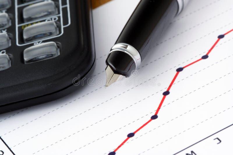 Pluma y calculadora en gráfico positivo de la ganancia foto de archivo libre de regalías
