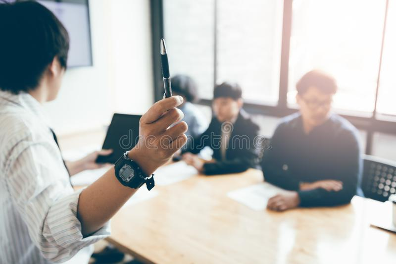 Pluma y enseñanza de tenencia de la persona del negocio con la reunión del personal en b imagen de archivo