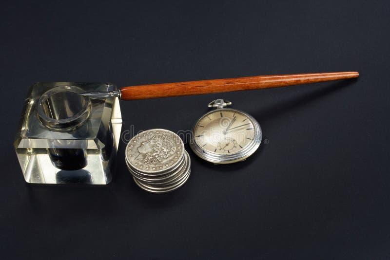 Pluma y tintero con las monedas de plata y reloj de bolsillo viejos en un fondo negro fotos de archivo libres de regalías