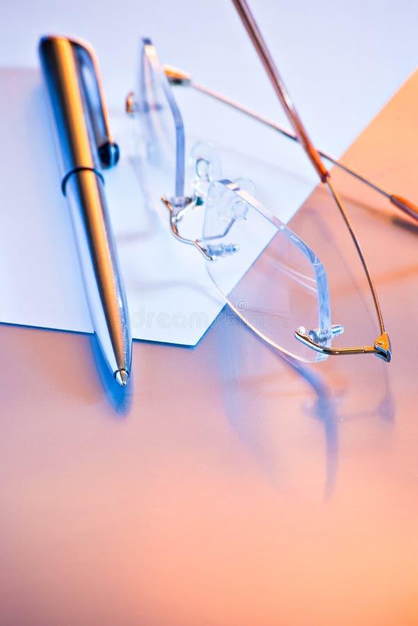Pluma y vidrios en el papel imagenes de archivo