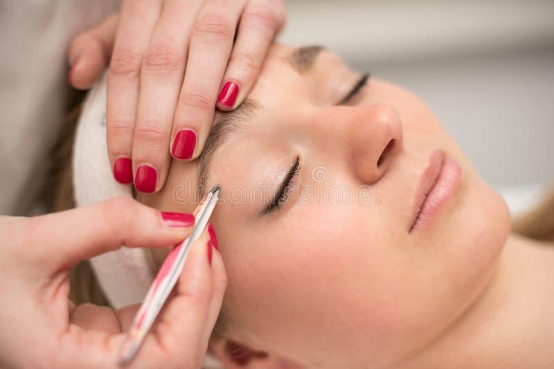 Plumaison des sourcils avec la brucelles par l'esthéticien dans le salon de beauté photos stock