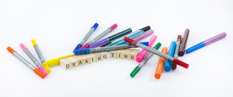 Plumas coloreadas con los cubos de madera que forman las palabras - tiempo del dibujo en un fondo blanco foto de archivo