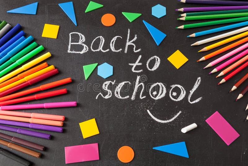 Plumas coloridas, lápices, título de nuevo a la escuela escrita por la tiza y figuras geométricas en la pizarra imágenes de archivo libres de regalías