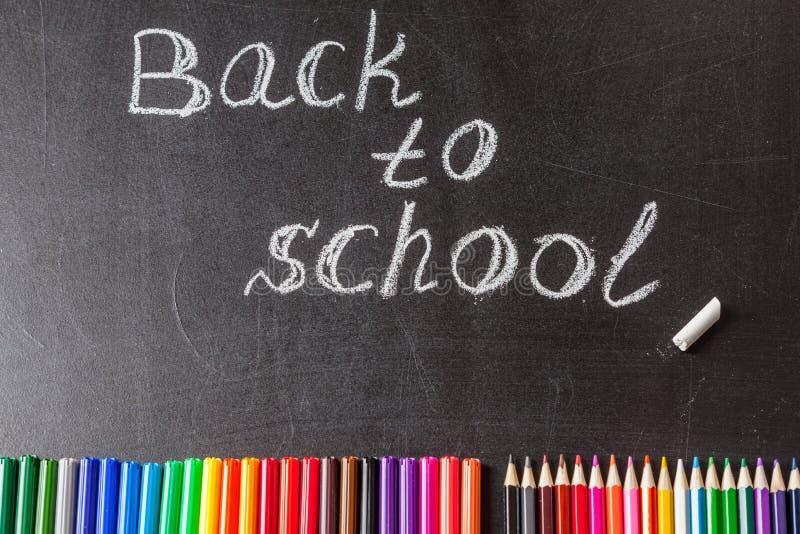 Plumas de extremidad de fieltro coloridas, lápices y el título de nuevo a la escuela escrita por la tiza blanca en la pizarra neg foto de archivo libre de regalías