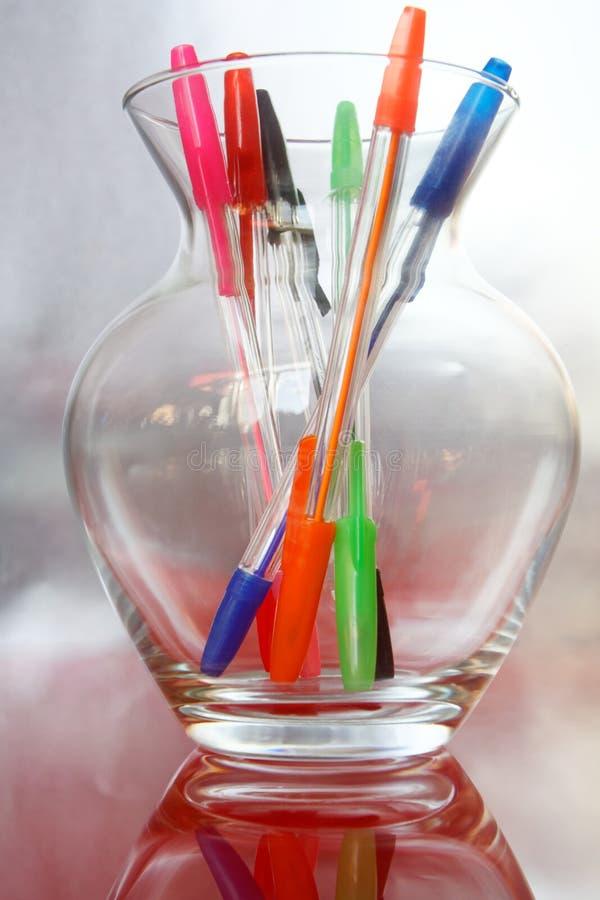Plumas multicoloras en un florero de cristal en una plata y un fondo rosado orderliness Trabajo en la oficina o la escuela foto de archivo libre de regalías
