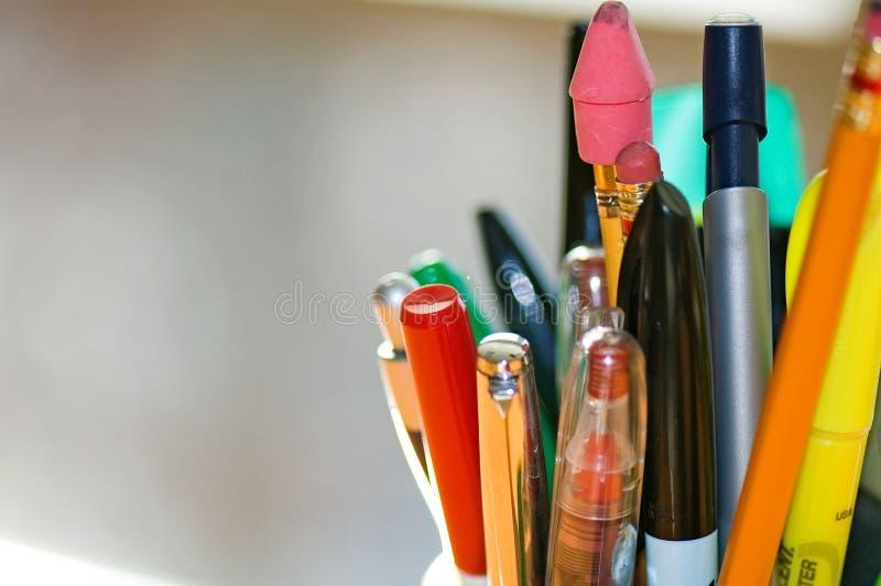 Plumas y lápices en el escritorio fotos de archivo