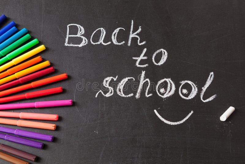 Plumas y título de la extremidad de fieltro coloridas de nuevo a la escuela escrita por la tiza en la pizarra negra de la escuela foto de archivo