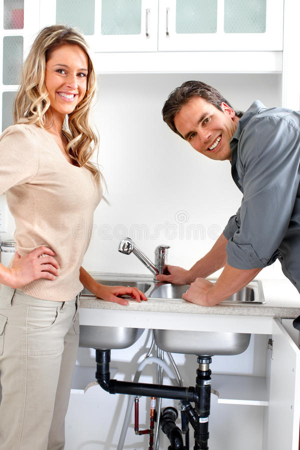Plumber. Young plumber fixing a sink stock images