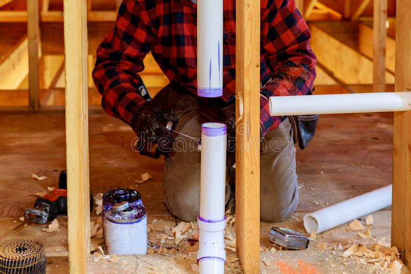 Plumber applying glue to PVC pipe under construction in new home royalty free stock photos