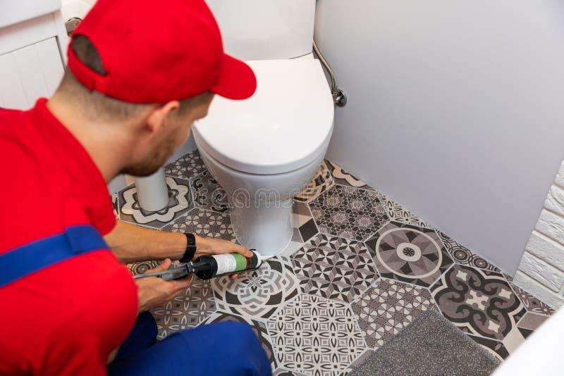 Plumber applying silicone sealant around water closet stock photo