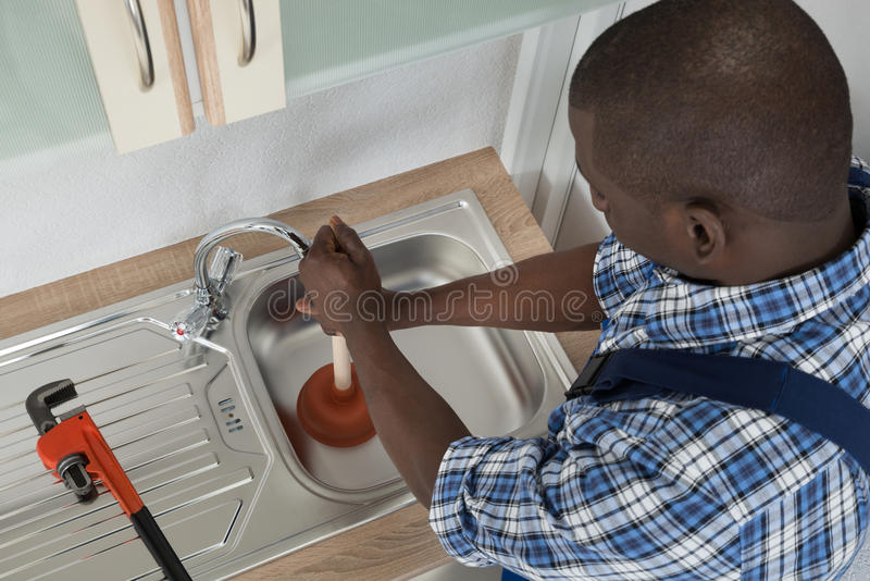 Plumber Cleaning Sink With Plunger. Close-up Of African Male Plumber Cleaning Sink With Plunger stock photo