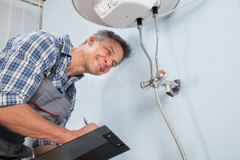 Plumber with clipboard looking at electric boiler royalty free stock image
