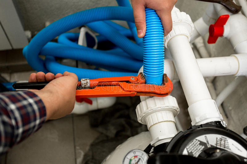 Plumber connecting two pipes with red pliers royalty free stock image