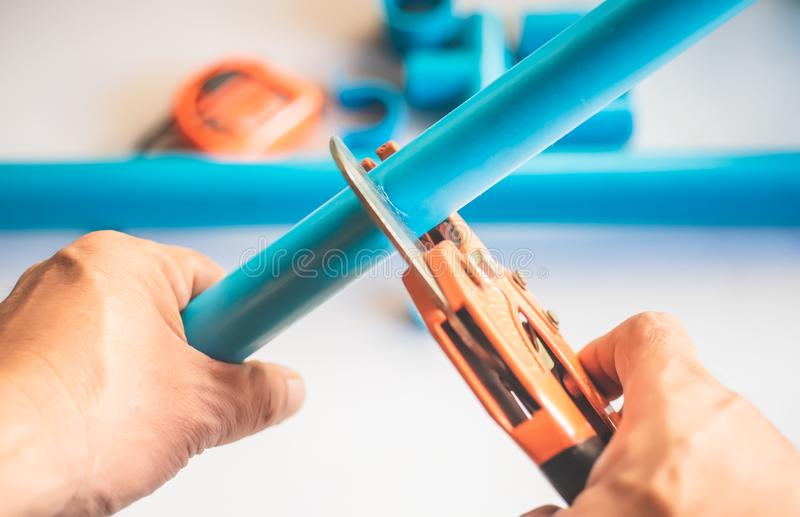 A plumber cut PVC pipe with PVC pipe cutting pliers tool .selective focus .Plumbing Repair and maintenance concept royalty free stock photography