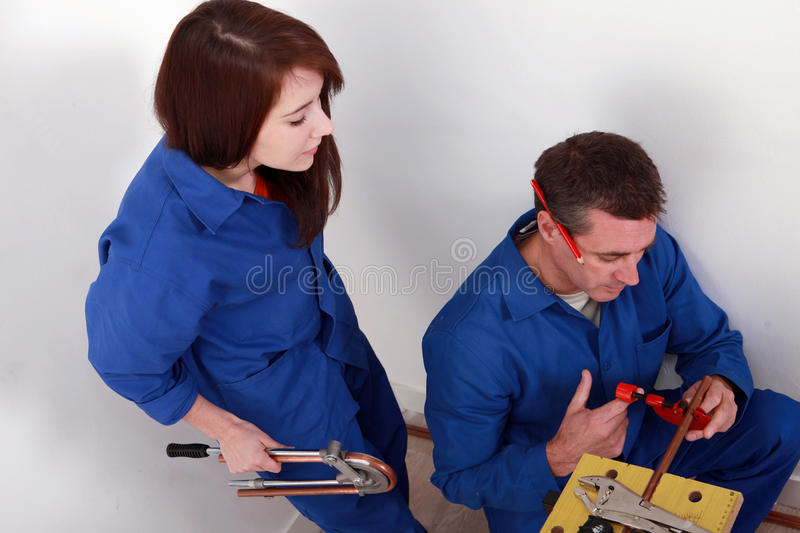 Plumber cutting copper pipe= stock photos