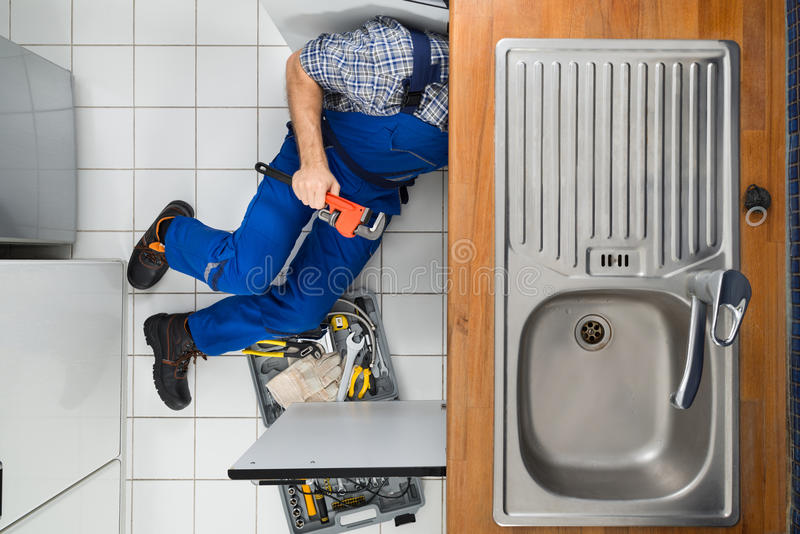 Plumber examining kitchen sink stock image