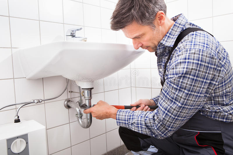 Plumber fitting sink pipe. Mature Male Plumber Fitting Sink Pipe In Bathroom royalty free stock photo