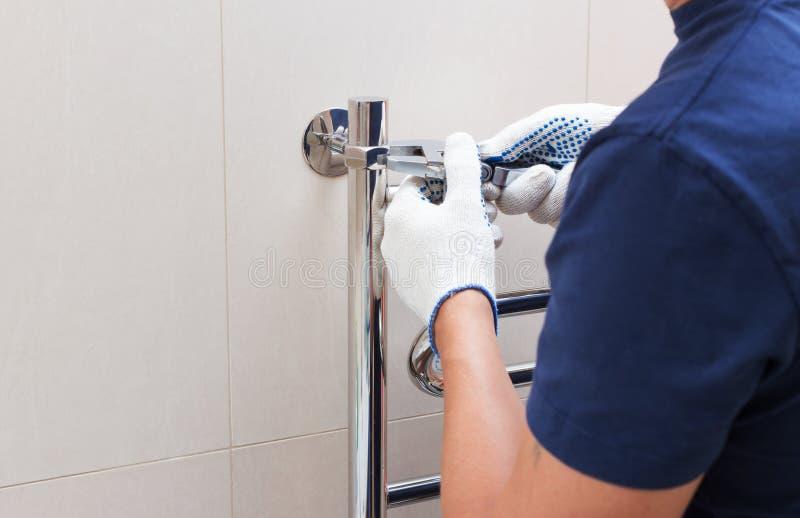 Plumber fixing chrome heated towel rail in bathroom.  stock photo