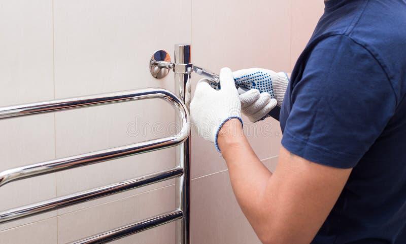 Plumber fixing chrome heated towel rail in bathroom royalty free stock photos