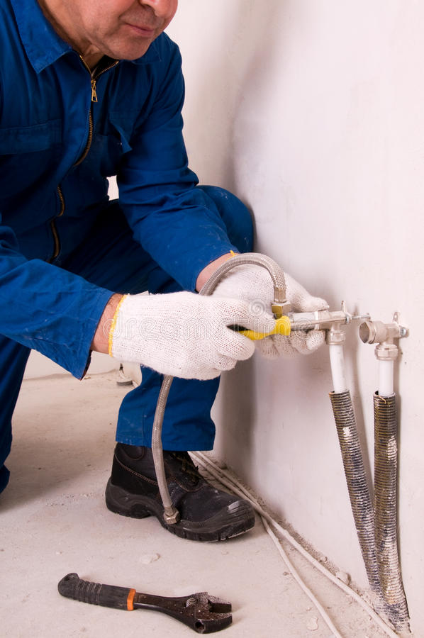 Plumber fixing water pipe. Senior Plumber fixing water pipe royalty free stock photography