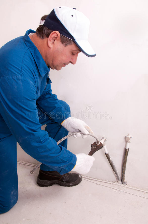 Plumber fixing water pipe. Senior plumber fixing water pipe stock photos