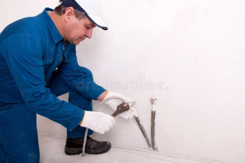 Plumber fixing water pipe. Senior plumber fixing water pipe royalty free stock photo