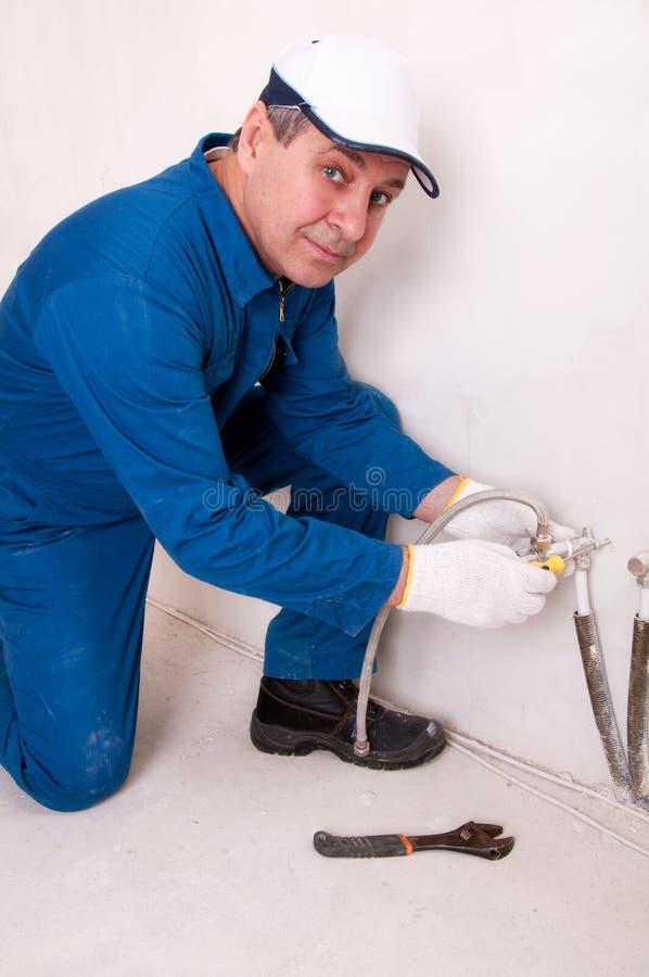 Plumber fixing water pipe. Senior plumber fixing water pipe royalty free stock image
