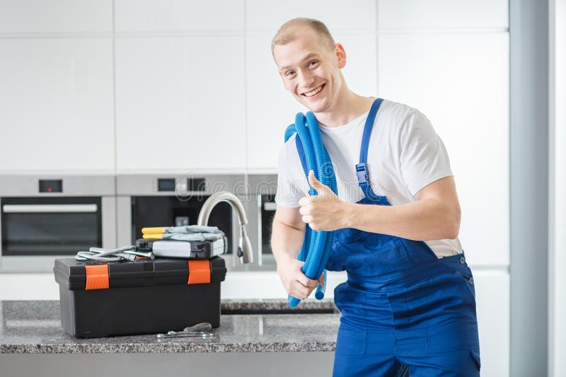 Plumber giving thumbs-up. Smiling plumber giving a thumbs-up to a customer standing next a tool box in a kitchen royalty free stock photography
