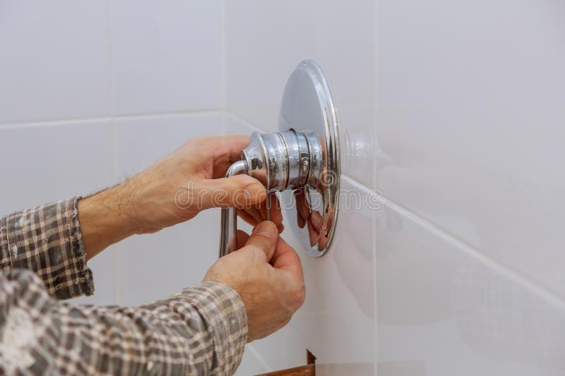 Plumber hands fixing shower mixer on modern water tap royalty free stock photography
