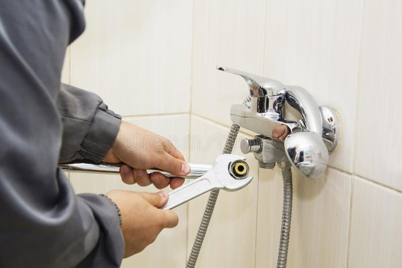 Plumber hands fixing water tap with spanner stock photography